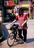 Beijing bicyclist wearing fashionable sun visor at the Silver Ingot Bridge in the Back Lakes area of hutongs