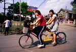Beijing teenagers on bicycle built for two at the Silver Ingot Bridge in the Back Lakes hutong area