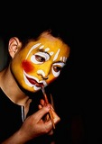 Beijing Opera wuchou or acrobatic clown character applying greasepaint makeup prior to performance at the Liyuan Theater