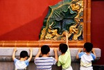 Shenyang Imperial Palace, curious boys examining glazed tile decoration on wall screen in palace courtyard