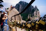Locks on railing of Huangshan's Jade Screen Terrace with Heavenly Capital Peak in background, placed by romantic couples
