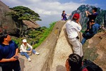 Chinese tourists at Huangshan's (Yellow Mountain's) Jade Screen Terrace taking photos with the Welcome Pine and Heavenly Capital Peak as backgrounds