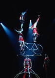 Shanghai Acrobats bicycle balancing act on stage of Magnolia Theater