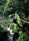 Elderly tourist on zip line through rain forest, aka The Canopy, in the Lake District's Parque Nacional Vicente Perez Rosales