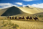 Dunhuang's Singing Sands Mountains dunes with tourists on camel caravan