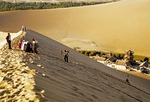 Dunhuang's Singing Sands Mountains with tourists climbing dunes above Crescent Moon Lake