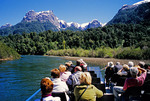 Tourists on boat cruise on river beneath peaks of Andes near Puerto Peulla in Lake District of Chile