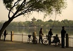Beijing back lake, Hou Hai, in early morning with local residents fishing and excercising with Wang Hai Lou, Watching the Sea Tower on opposite shore