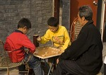 Children playing Chinese chess in hutong neighborhood along Beijing's back lake, Hou Hai