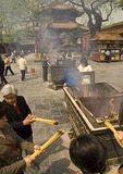The Lama Temple (Yonghe Gong) with worshippers placing joss sticks in incense burners near entrance