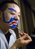 Beijing Opera performer applying grease paint prior to performance at the Liyuan Theater