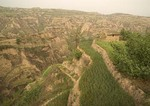 Eroded landscape of loess plateau with farm terraces near Yellow River (Huanghe) in Shanxi province