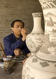 Artisan decorating ceramic vase in workshop in Xian