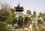 Suzhou's Pan Men Park with pagoda and pavilion above rockery waterfall and spring blossums