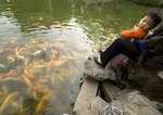 Suzhou's Lingering Garden (Liu Yuan), child watching goldfish in pond