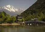 Lijiang's Black Dragon Pool with Moon-Embracing Pavilion and Belt Bridge with Jade Dragon Snow Mountain in background