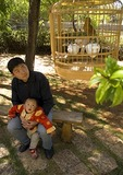 Lijiang young father holding child watching caged bird in park