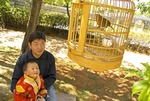 Lijiang young father holding child watching caged bird in Black Dragon Pool park