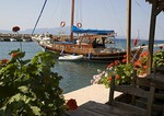 Sailboat in Assos harbor with dockside restaurant