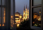 Blue Mosque through hotel window at dawn with Aya Sofya relected in window
