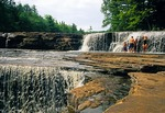 Family cooling off in summer at lower falls at Tahquamenon Falls State Park