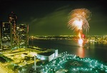 Annual summer fireworks event over Detroit River with Renaissance Center and crowd in Hart Plaza