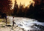 Boys fishing in autumn at Ocqueoc Falls, largest in lower peninsula of Michigan