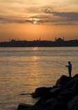 Istanbul fisherman at sunset on Asia side across Bosphorus from Aya Sofya (Hagia Sophia, Church of the Holy Wisdom) and skyline of Istanbul