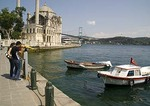 Promenade along Istanbul's Bosphorus with boats, Ortakoy Mosque, and Bosphorus Bridge