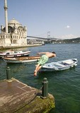 Young man diving into Istanbul's Bosphorus with boats, Ortakoy Mosque, and Bosphorus Bridge