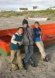 Boys on beach with boats at South African fishing village of Paternoster on Atlantic coast