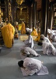 Devotees kneel in prayer at Vinh Trang Pagoda Buddhist temple at My Tho in the Mekong River Delta