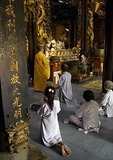 Devotees kneel in prayer with monk at Vinh Trang Pagoda Buddhist temple at My Tho in the Mekong River Delta