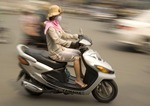 Downtown Saigon fashionable young woman on speeding motor bike