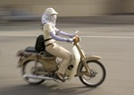 Fashionable young woman on speeding motor bike in Mekong River Delta south of Saigon
