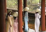 Young Vietnamese women wearing traditional ao dai dress and conical hat at The Citadel Imperial Palace in Hue