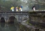 Young Vietnamese women with umbrellas wearing traditional ao dai dresses crossing stone bridge at Hue's Luu Kheim Lake in the Royal Mausoleum complex of Nguyen emperor Tu Duc