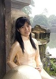 Young Vietnamese woman wearing traditional ao dai dress at Hue's Xung Kheim Pavilion on Luu Kheim Lake in the Royal Mausoleum complex of Nguyen emperor Tu Duc