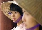 Young Vietnamese women wearing traditional ao dai dress and conical hat in Hue