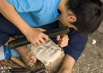 Young craftsman at work in wood carving shop in Old Town of Hoi An