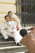 Bride and groom pose for wedding photos on steps of French colonial Hanoi Opera House