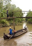 Long boat passing under footbridge over canal in the Mekong River Delta near Can Tho