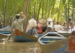 Paddling backwaters of Mekong River Delta on canal tour near Ben Tre