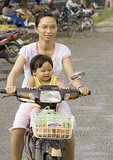 Mother with child on motor bike in Mekong River Delta