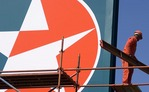 Caltex petrol station workman on scaffolding for company sign in Western Cape
