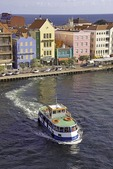 Willemstad's Punda waterfront, the Handelskade, pastel Dutch architecture with ferry for pedestrians crossing Sint Ana Baai entrance