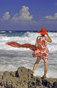 Aruba's windswept rocky west end shore with woman in red