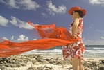 Woman with red scarf at Aruba's windswept northwest tip near California Dunes and Lighthouse