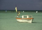 Aruba windsurfer and colorful boat off west shore of island
