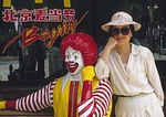 Pretty Chinese woman with statue of Ronald McDonald at fast food outlet in Beijing